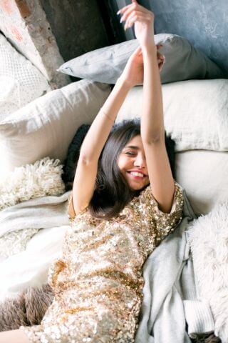 Woman smiling in bed with her arms raised