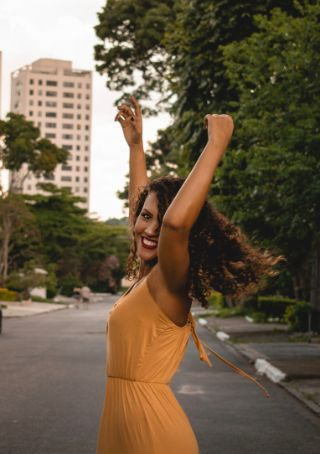 Woman smiling and raising her arms into the air with positivity.