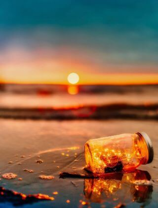 Broken jar on the beach with lights inside symbolizing replacing cynicism with positivity.