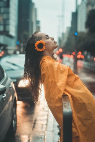 Woman leaning back in rain with her eyes closed