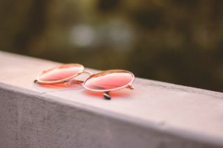 Rose-colored glasses sitting on a concrete ledge