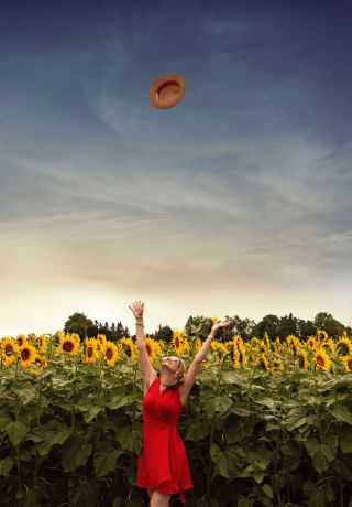 Woman in red dress in a field of sunflowers throwing her hat into the air.