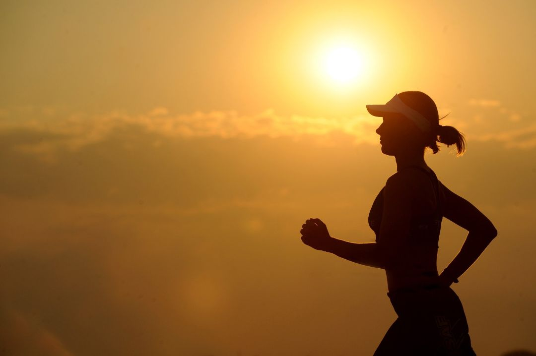 Silhouette of woman running, symbolizing she knows how to stay positive in the face of adversity.