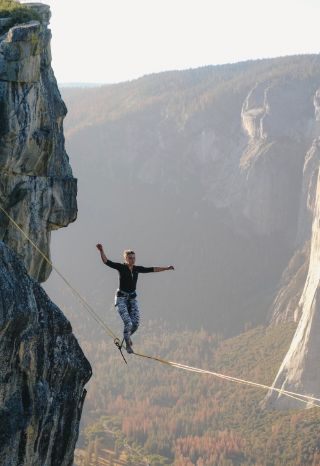 Woman walking a tightrope above a valley without fearing failure.