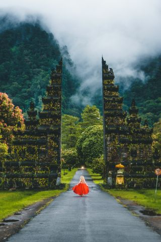 Woman in a red dress about to walk through a giant gate, symbolizing you can start your journey to learn how to stop doubting yourself.