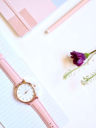 pink watch and purple flower on white surface, symbolizing you have time to do what you want with your life
