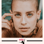 woman with shaved head staring into camera