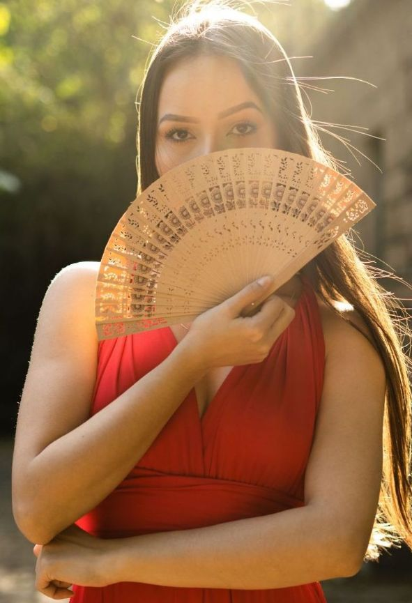 woman covering her face with a fan