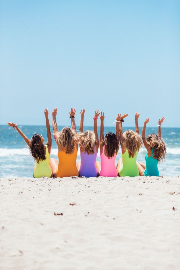 group of girls raising their hands up on the beach