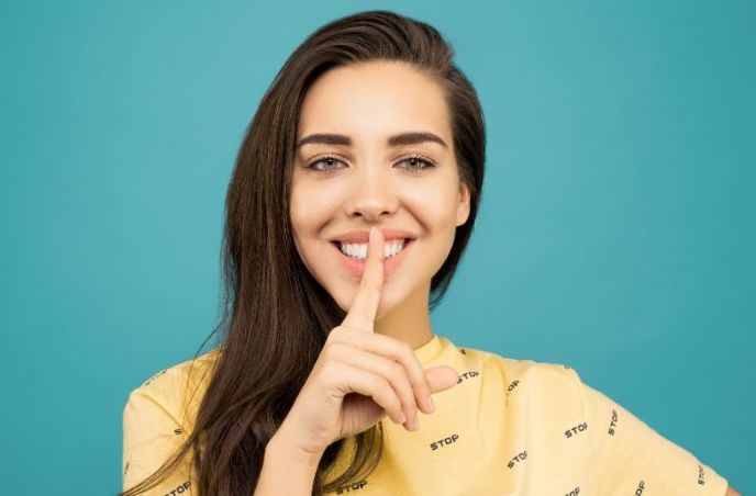 woman smiling with finger on mouth