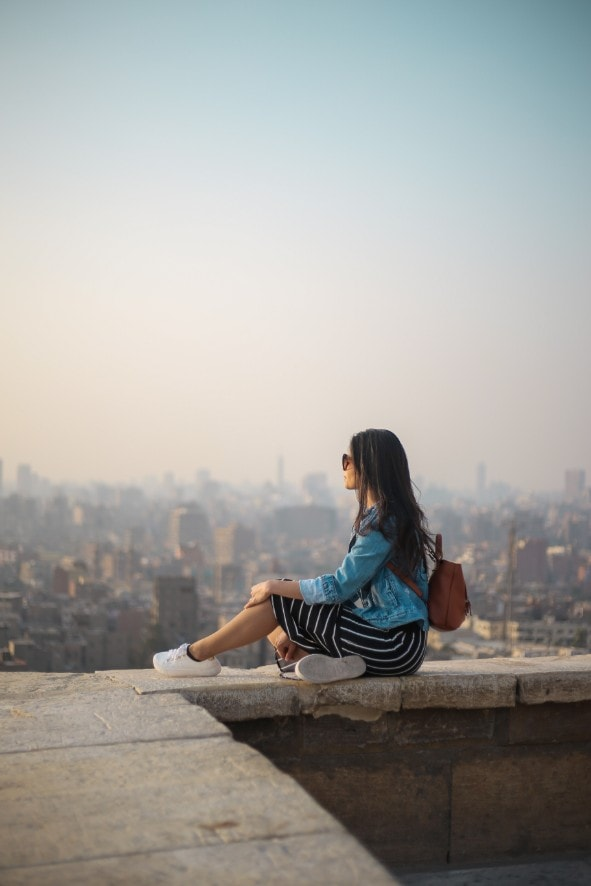 woman with anxiety sitting on ledge overlooking city