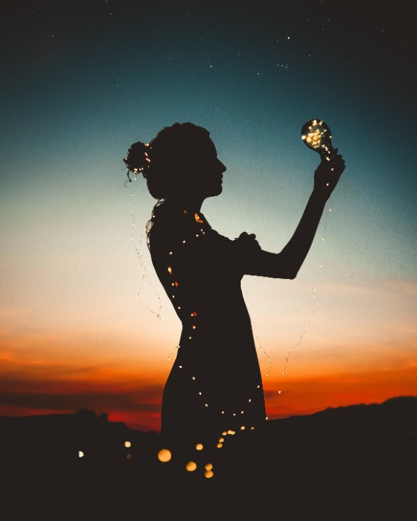 silhouette of woman holding light bulb