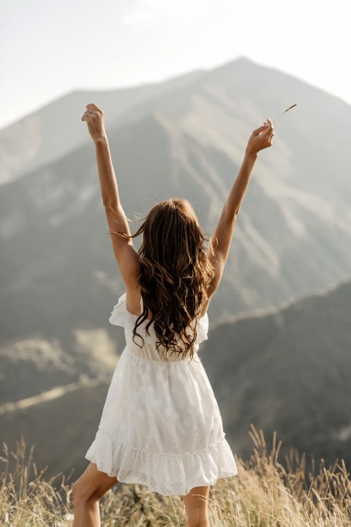 woman raising arms in front of meadow